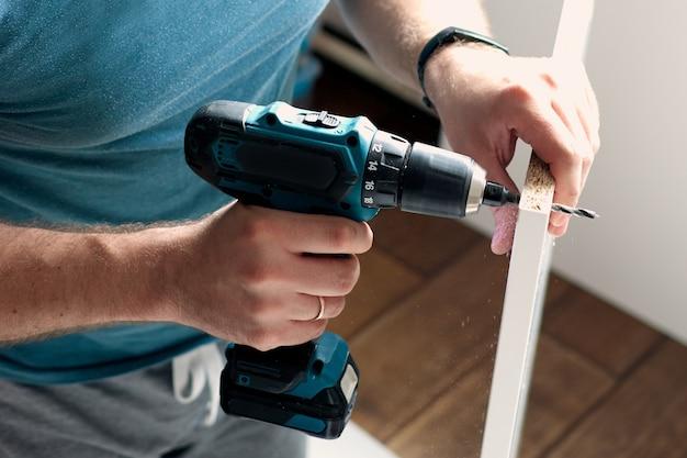 Uomo che fa lavori di ristrutturazione a casa foratura con un cacciavite