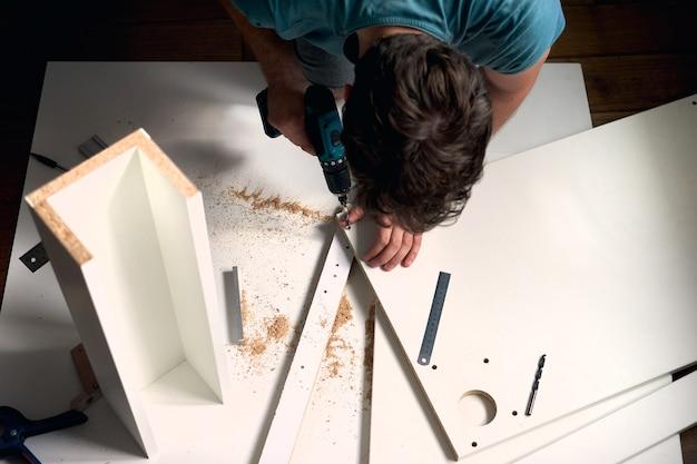 Uomo che fa lavori di ristrutturazione a casa, misurando un pezzo di legno