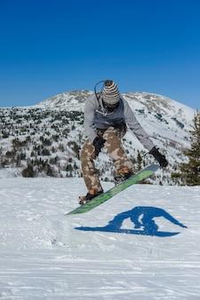 L'uomo facendo snowboard salto sullo sfondo delle montagne