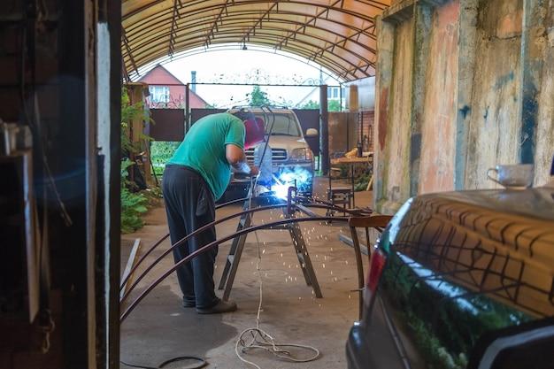 Un uomo che fa saldatura a punti sotto la tettoia del suo garage. le scintille volano via.