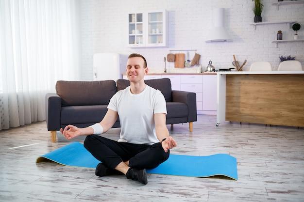 Un uomo che fa esercizi di yoga a casa, seduto sul pavimento del soggiorno. uno stile di vita sano.