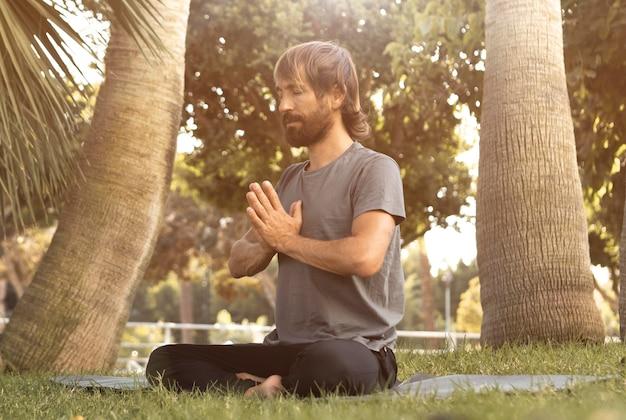 Uomo che fa yoga sull'erba all'aperto