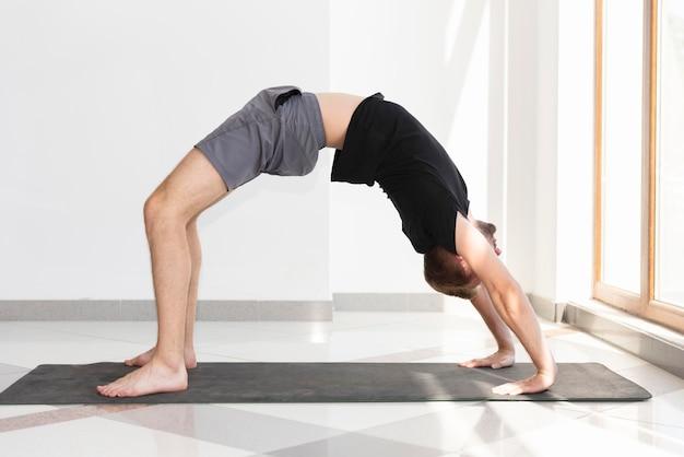 Uomo che fa yoga al coperto