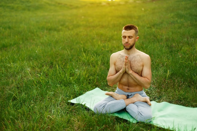 Uomo che fa yoga nel parco sulla natura. meditazione