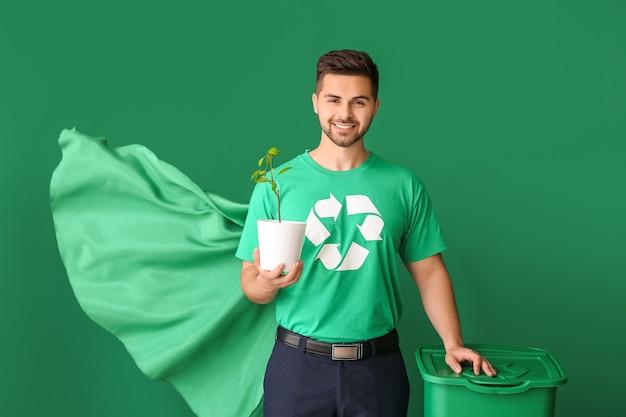 Uomo vestito da supereroe eco con cestino e pianta sul colore