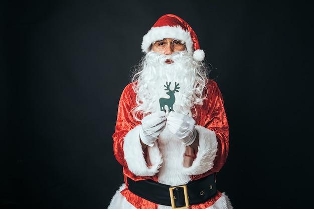 Uomo vestito da babbo natale che tiene una figura in legno di renne, su sfondo nero. concetto di natale, babbo natale, regali, celebrazione.