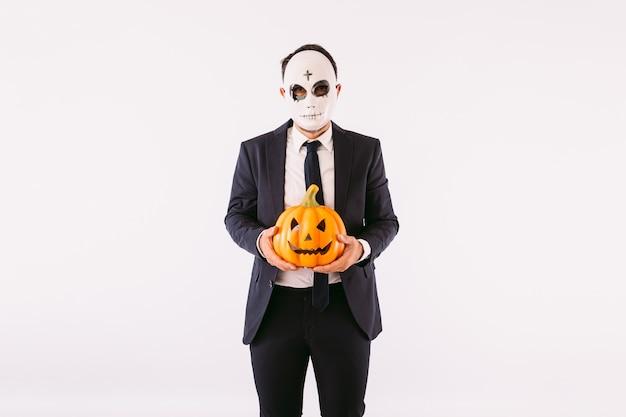 Uomo vestito in giacca e cravatta, che indossa una maschera da killer con le sopracciglia incrociate di halloween, con in mano una zucca jack-o-lantern. carnevale e festa di halloween
