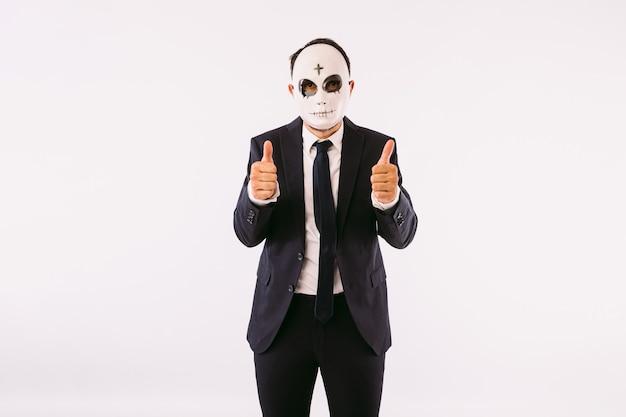 Uomo vestito in giacca e cravatta, che indossa una maschera killer di halloween con la fronte incrociata, pollice in alto. carnevale e festa di halloween