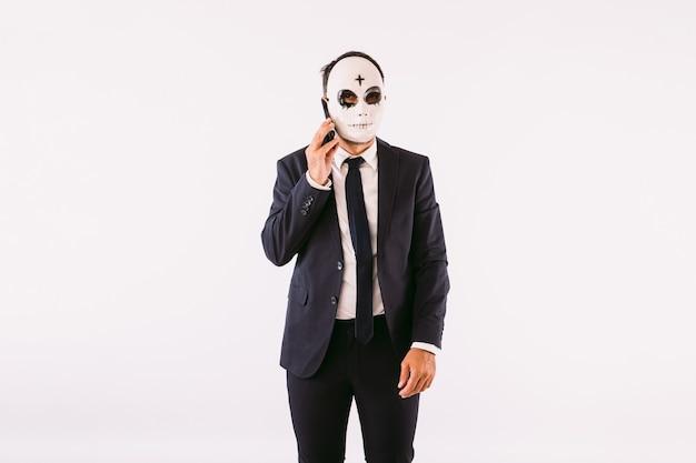 Uomo vestito con giacca e cravatta, che indossa una croce di halloween sulla sua maschera killer sulla fronte, parla al telefono cellulare. carnevale e festa di halloween