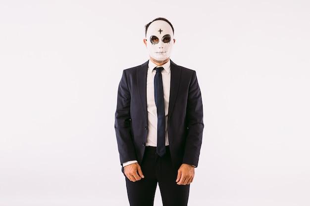 Uomo vestito con giacca e cravatta, che indossa una maschera da killer con una croce sulla fronte per halloween. carnevale e festa di halloween