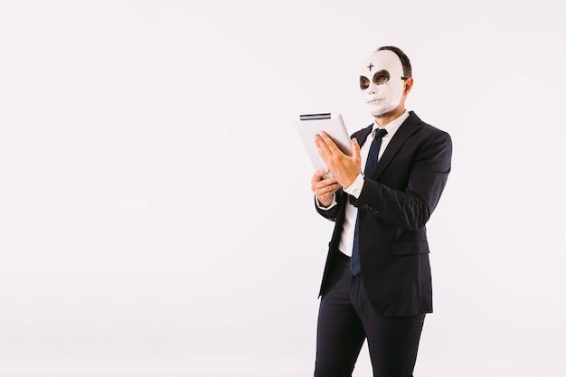 Uomo vestito in giacca e cravatta, che indossa la maschera di un killer con una croce sulla fronte per halloween, guardando il suo tablet. carnevale e festa di halloween