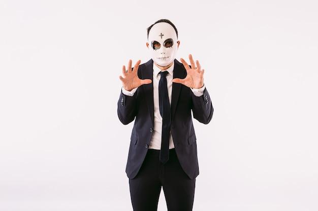 Uomo vestito con giacca e cravatta, che indossa una maschera da killer con una croce sulla fronte per halloween, che spaventa con le mani. carnevale e festa di halloween