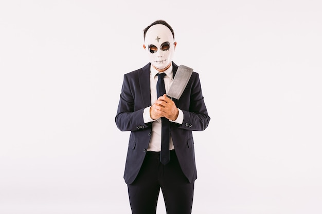 Uomo vestito in giacca e cravatta, che indossa una maschera da killer con una croce sulla fronte per halloween, minaccia con un coltello. carnevale e festa di halloween