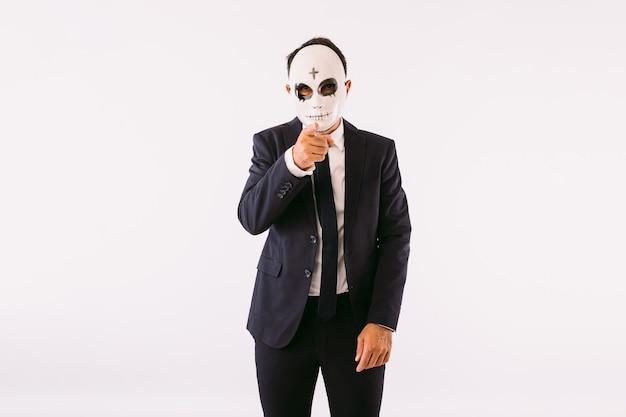 Uomo vestito in giacca e cravatta che indossa una maschera da killer con una croce sulla fronte per halloween