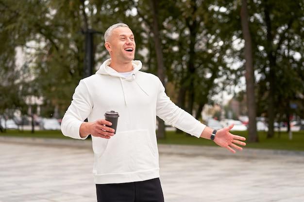 L'uomo vestito di felpa con cappuccio bianca con caffè in mano