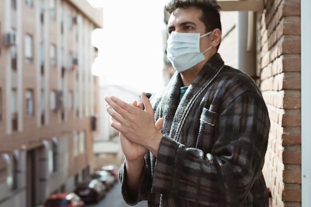 Uomo in vestaglia, pigiama e maschera che applaude le persone che stanno combattendo contro il coronavirus (covid19) dalla terrazza al tramonto
