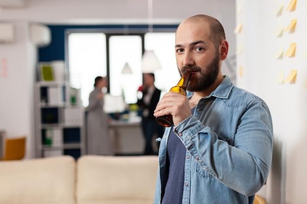 Uomo che beve una bottiglia di birra dopo una riunione di lavoro