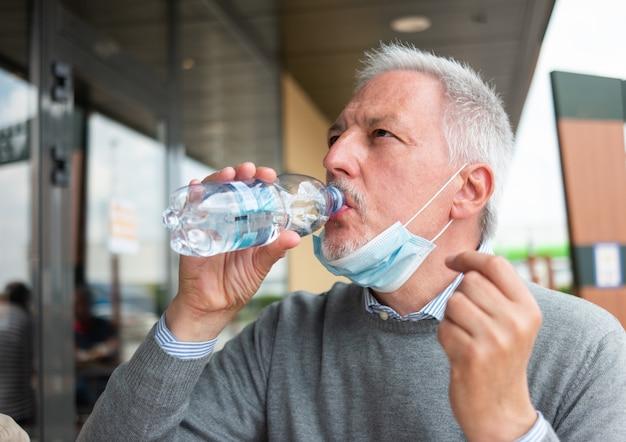Uomo che beve una bottiglia d'acqua