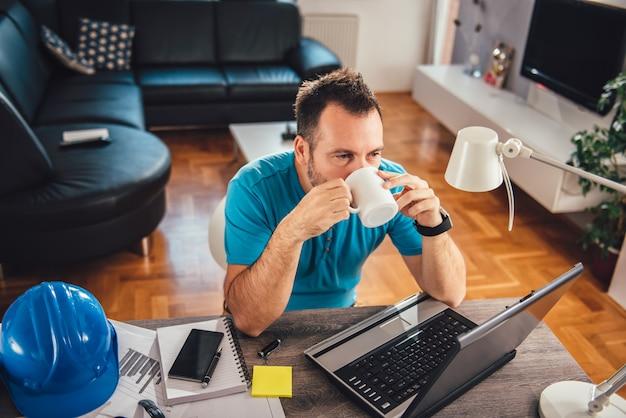 Uomo che beve l'ufficio del caffè a casa
