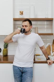 Uomo che beve caffè in cucina