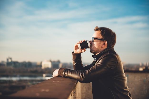 Uomo che beve il caffè sul tetto