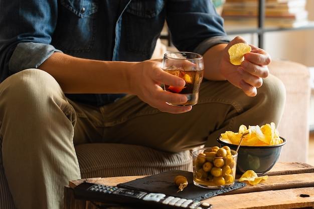 Uomo che beve vermouth e mangia snack dopo il lavoro a casa Foto Premium