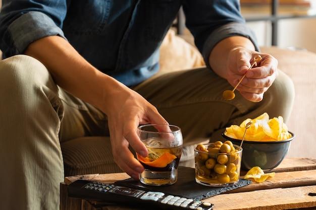 Uomo che beve vermouth e mangia snack dopo il lavoro a casa work