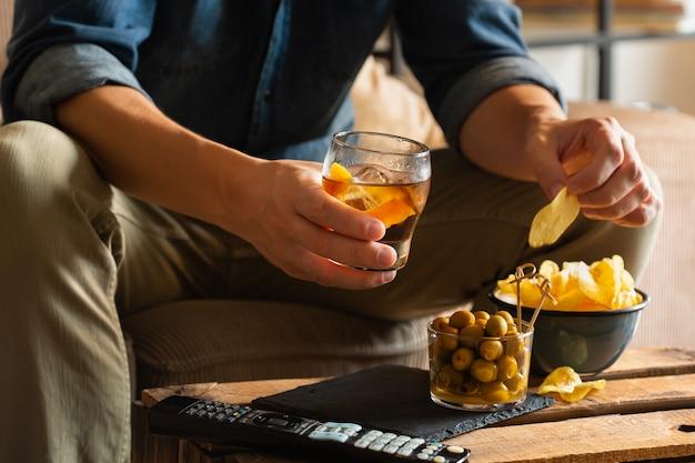 Uomo che beve vermouth e mangia snack dopo il lavoro a casa