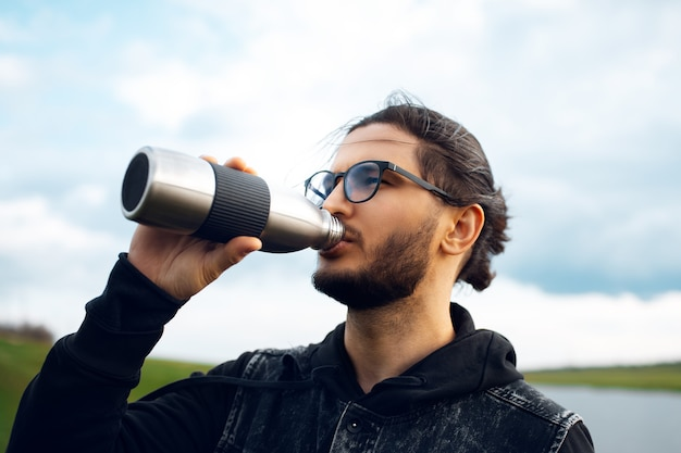 Uomo che beve acqua da una bottiglia termica in acciaio riutilizzabile sullo sfondo di un cielo nuvoloso sfocato