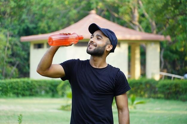 Un uomo che beve acqua nel parco