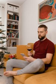 Uomo che beve vino mentre è seduto sul divano di casa