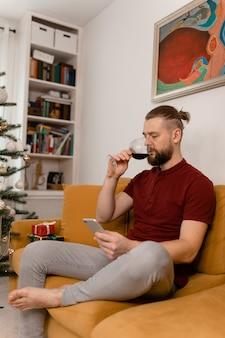 Uomo che beve vino mentre è seduto sul divano in salotto
