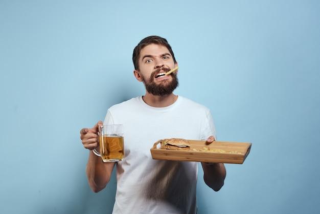 Un uomo beve birra da un bicchiere e mangia fast food
