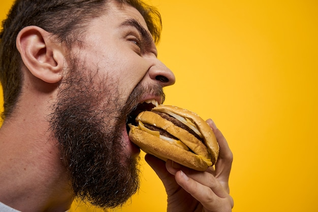 Un uomo beve birra da un bicchiere e mangia fast food fritto spazzatura