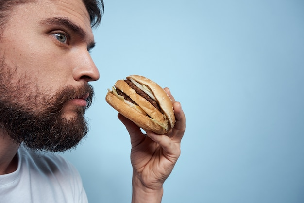 Un uomo beve birra da un bicchiere e mangia cibi fritti spazzatura