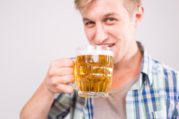 L'uomo beve birra. bel giovane ragazzo che beve pinta di birra chiara su sfondo bianco.