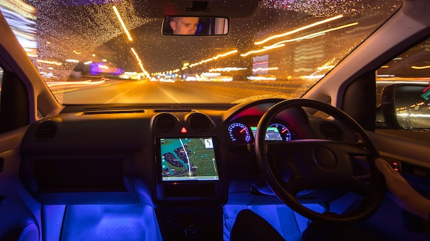 L'uomo guida l'auto nella città notturna. traffico a sinistra. vista interna