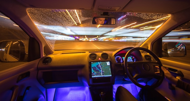 L'uomo guida l'auto nella città della pioggia. traffico a sinistra. serata notturna