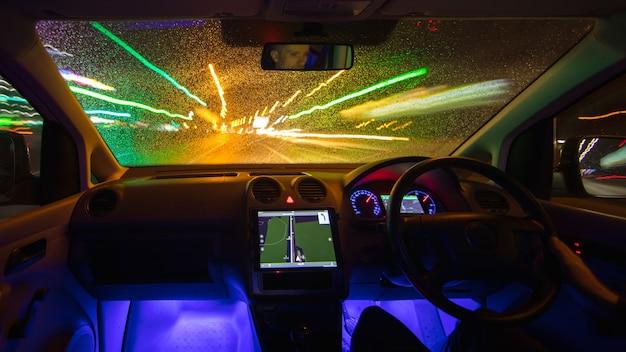 L'uomo guida l'auto nella città piovosa. traffico a sinistra. serata notturna