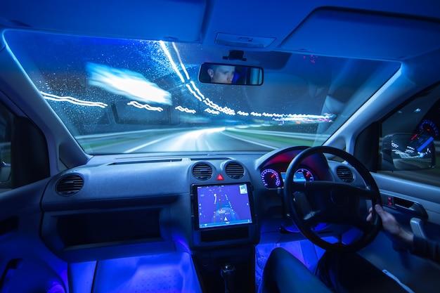 L'uomo guida un'auto con un gps in una città. serata notturna. traffico a sinistra