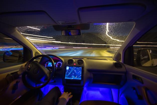 L'uomo guida sull'autostrada della pioggia. serata notturna. vista interna