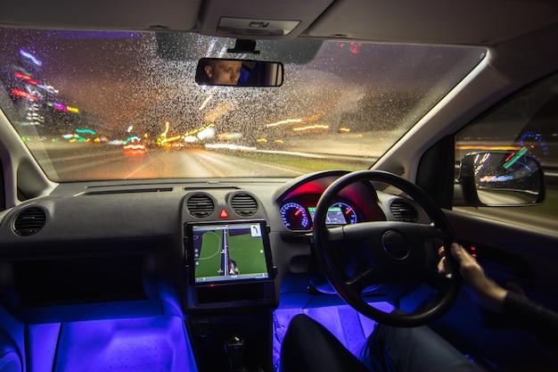 L'uomo guida il veicolo nell'autostrada della città. traffico a sinistra. serata notturna