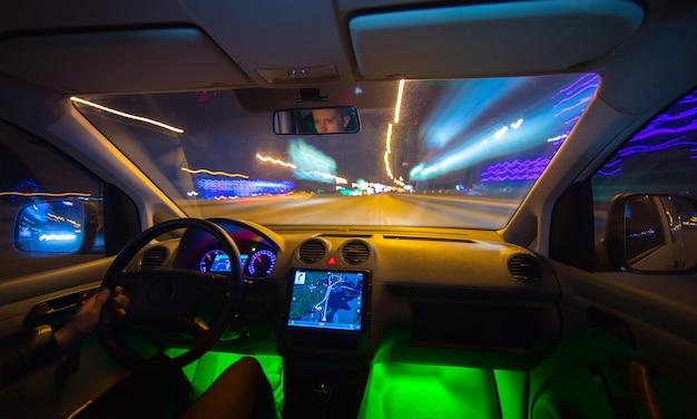 L'uomo guida un veicolo sulla strada notturna. vista interna. angolo ampio