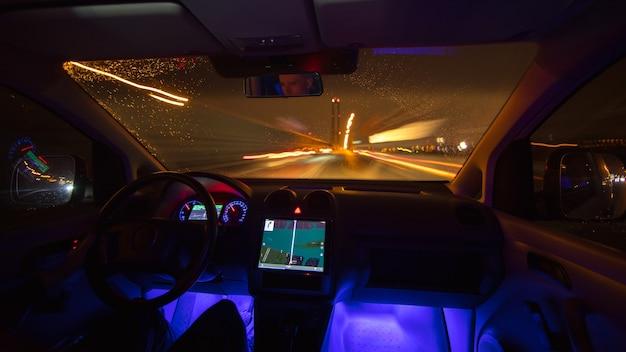 L'uomo guida con un gps nella città notturna. vista interna