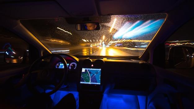 L'uomo guida con un gps sulla strada notturna. vista interna. angolo ampio
