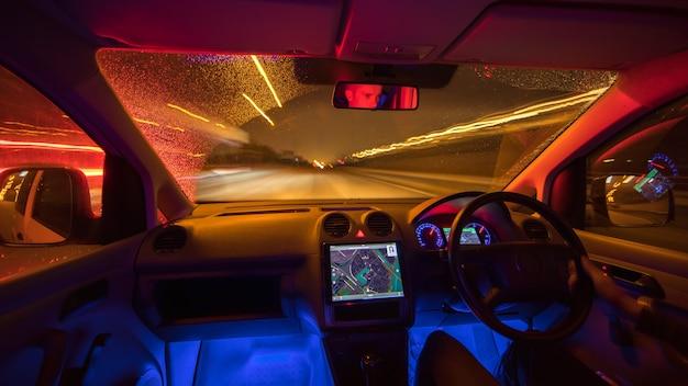 L'uomo guida con una mappa su una strada piovosa. serata notturna. traffico a sinistra
