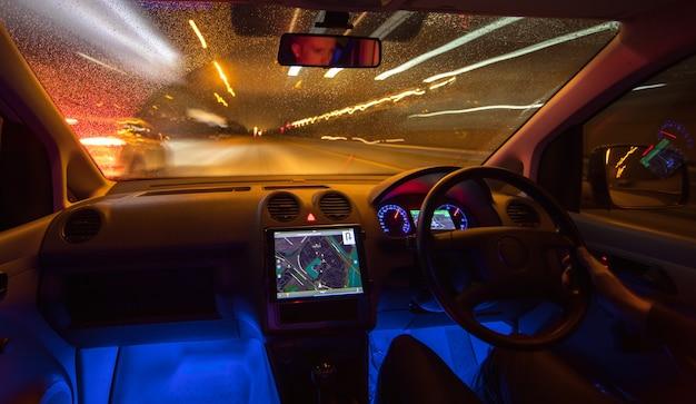 L'uomo guida con una mappa sulla strada. serata notturna. traffico a sinistra