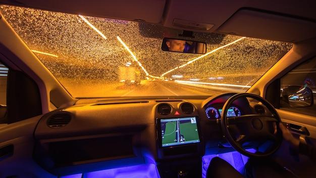 L'uomo guida con la navigazione in città. traffico a sinistra. serata notturna