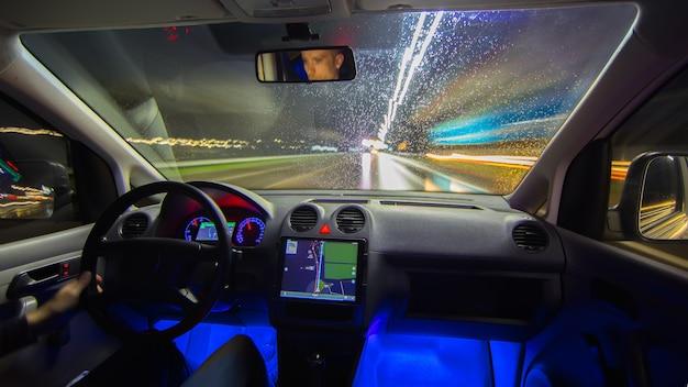 L'uomo guida con un navigatore sull'autostrada notturna. vista interna
