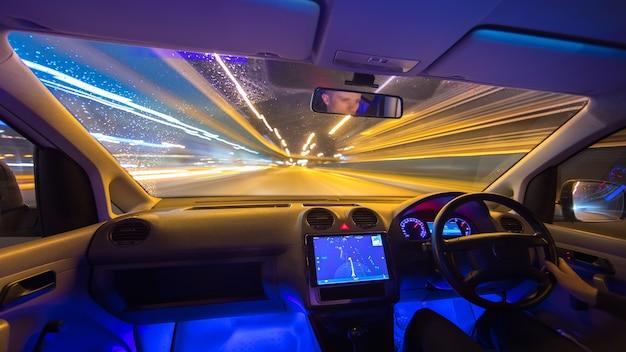 L'uomo guida con una navigazione su un'autostrada della pioggia. traffico a sinistra. angolo ampio